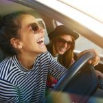 southcoastcounseling-can-i-still-have-fun-if-i-travel-while-sober-photo-of-a-laughing-young-woman-wearing-sunglasses-inside-the-car