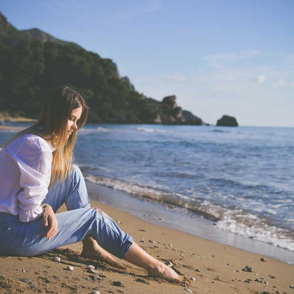 southcoastcounseling-ptsd-and-addiction-photo-of-a-lonely-woman-sitting-on-the-beach,-thinking,-looking-at-the-sand